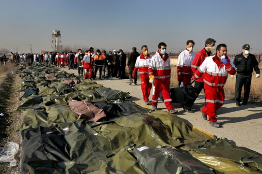 Rescue workers carry the body of a victim of a Ukrainian plane crash in Shahedshahr, southwest of the capital Tehran, Iran,, Jan. 8, 2020.