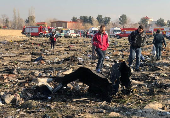 People walk near the wreckage after a Ukrainian plane crashed near Imam Khomeini airport in Tehran early in the morning on January 8, 2020, killing everyone on board. The Boeing 737 had left Tehran's international airport bound for Kiev, semi-official news agency ISNA said, adding that 10 ambulances were sent to the crash site.