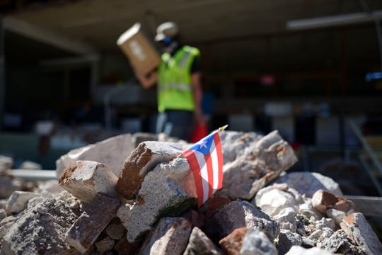 A Puerto Rican flag hangs within the rubble, after it was placed there, where store owners and family help remove supplies from Ely Mer Mar hardware store, witch partially collapsed after an earthquake struck Guanica, Puerto Rico, Tuesday, Jan. 7, 2020. A 6.4-magnitude earthquake struck Puerto Rico before dawn on Tuesday, killing one man, injuring others and collapsing buildings in the southern part of the island.