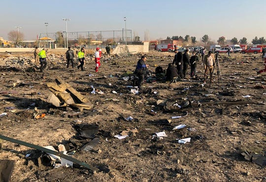 People and rescue teams are pictured amid the wreckage after a Ukrainian plane crashed near Imam Khomeini airport in the Iranian capital Tehran.