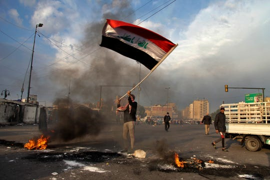A protester waves the national flag while demonstrators set fire to close streets near Tahrir Square in Baghdad, Iraq, on Jan. 8, 2020.