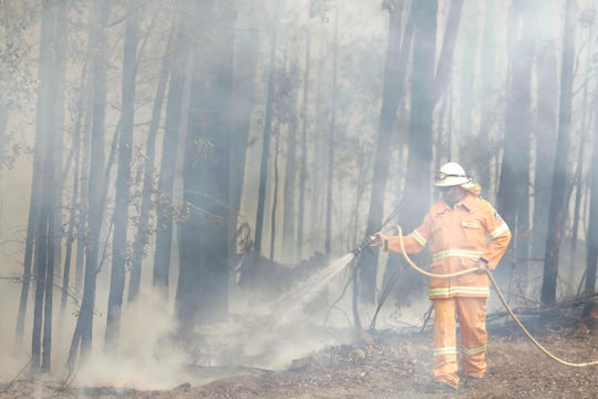 A firefighter is shrouded in smoke as he manages a controlled burn near Tomerong, Australia, Wednesday, Jan. 8, 2020, in an effort to contain a larger fire nearby.