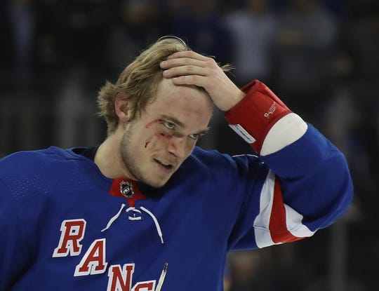 New York Rangers defenseman Ryan Lindgren leaves the ice after a fight with Nazem Kadri.
