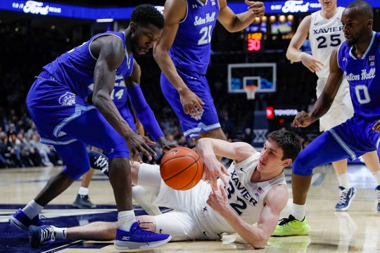 Xavier's Zach Freemantle (32) and Seton Hall's Myles Cale, left, scramble for a loose ball
