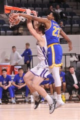ACU's Hayden Howell, left, dunks the ball as McNeese's Sha'markus Kennedy defends in the first half. McNeese won the Southland Conference game 87-84 Wednesday at Moody Coliseum.