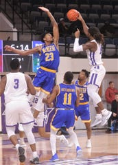 McNeese's Sha'markus Kennedy (23) tries to block a shot by ACU's Trey Lenox in the first half. Kennedy scored 24 points, grabbed 10 rebounds and had 6.5 blocks as the Cowboys upset ACU 87-84 in the Southland Conference game Wednesday at Moody Coliseum.
