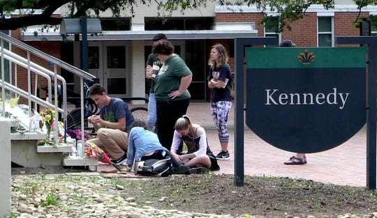FILE - In this May 3, 2019 file photo taken from video people pay respects at a makeshift memorial set up on the steps of the Kennedy Building on the campus of UNC Charlotte in the aftermath of a deadly classroom shooting in the building days earlier.  (David T. Foster III/The Charlotte Observer via AP, File)