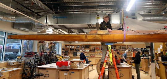 Mo Ellis stands atop a ladder as he prepares to release one of the pulleys holding the historic Quinault rowing shell aloft in the woodworking shop of BARN on Wednesday.