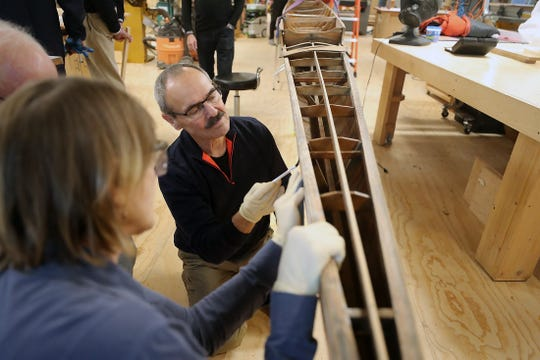 Mike Gearheard and fellow volunteers work on stripping the finish off of the stern of the historic Quinault rowing shell in the woodworking shop at BARN on Wednesday. BARN woodworkers and Bainbridge Island Rowing members are refinishing the shell for display in the Stan Pocock Legacy Rowing Center being built at Waterfront Park on Bainbridge.