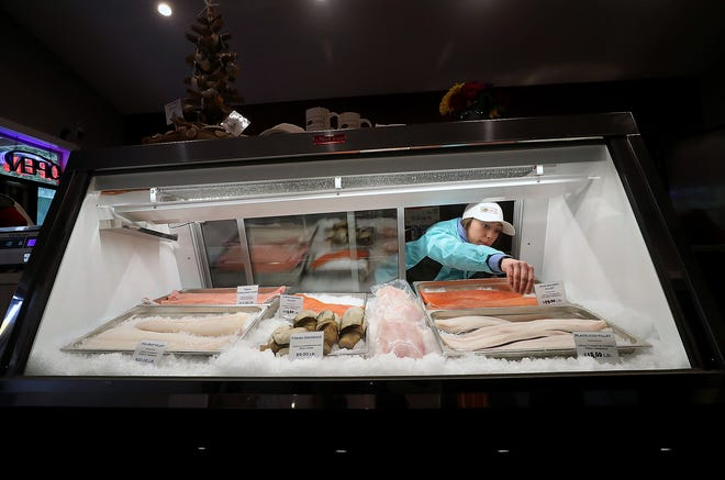 Retail manager Shaylene Jefferson reaches into the front case — filled with fresh fish and geoduck — to straighten one of the price signs during the grand opening celebration at Suquamish Seafoods retail store on Thursday.