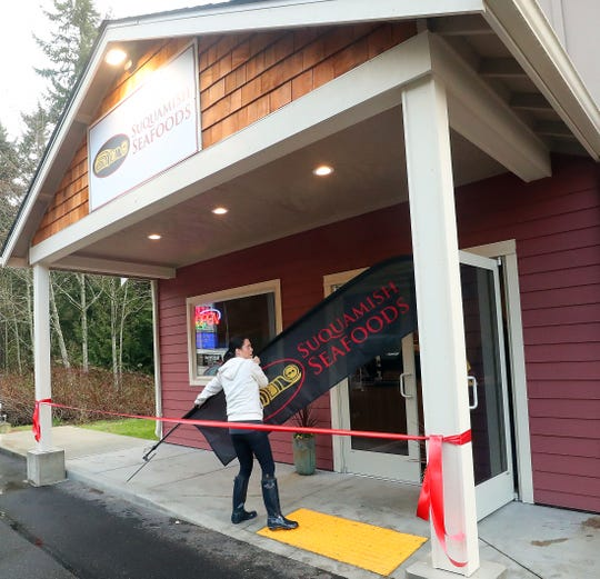 Shanel Carlson carefully maneuvers a large Suquamish Seafoods banner out of the front door to place near the road prior to the start of the grand opening celebration at Suquamish Seafoods retail store on Thursday.