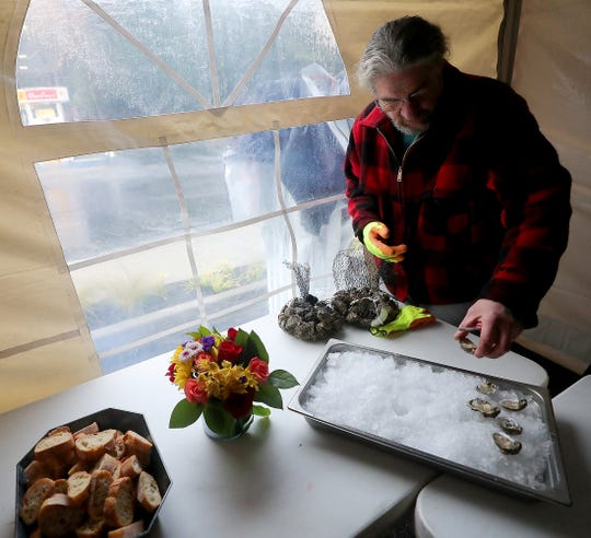 Plant manager Gary Severson shucks oysters inside the tent during the grand opening celebration at Suquamish Seafoods retail store on Thursday.