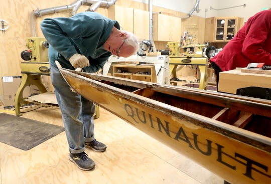 Bill Booth, of Bainbridge Island, scrapes the cracked finish off of the bow of the historic Quinault rowing shell in the woodworking shop at BARN on Wednesday. BARN woodworkers and Bainbridge Island Rowing members are refinishing the shell for display in the Stan Pocock Legacy Rowing Center being built at Waterfront Park on Bainbridge.