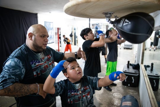 Coach Joe DeLaPaz helps 8-year-old Sergio Barrera use a speed bag at Duke it Out Boxing on Wednesday, Jan 9, 2019.
