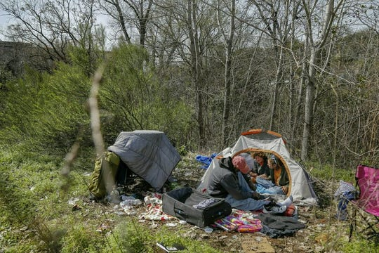 In this Wednesday, Feb. 13, 2019 file photo, from left, Terry Flakes, Kim Smith, and Tracy Botlinger have lunch at their camp in south Austin, Texas. Texas' Republican Gov. is creating a homeless campsite on state land amid an escalating battle with liberal leaders in the state capital over people living on the streets