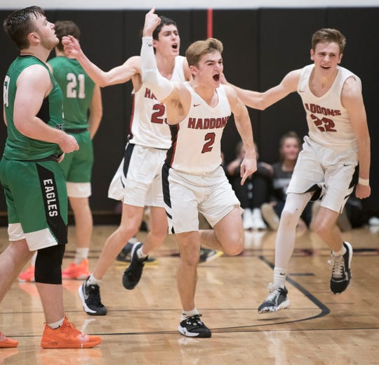 Haddonfield's Connor Fell, center, celebrates with teammates Andrew Gostovich, left, and Justin Kasko, right, after Haddonfield defeated West Deptford, 41-39, in overtime of the boys basketball game played at Haddonfield High School on Wednesday, January 8, 2020.