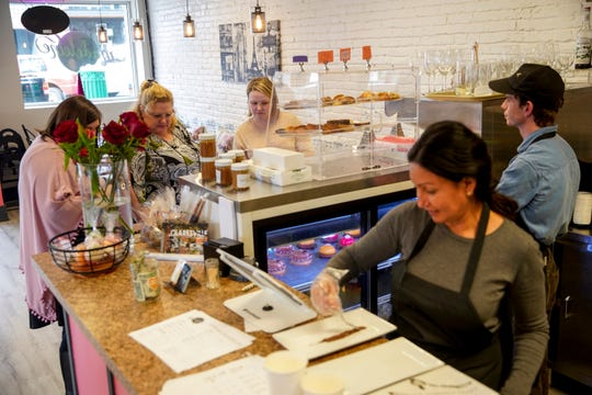 Owner Haja Bosela prepares plates while customers look through a display area at the counter for tarts and pastries at Madeleines Place in Clarksville, Tenn., on Thursday, Jan. 9, 2020.