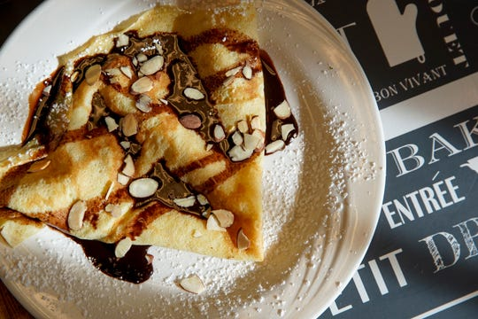 A simple crepe topped with chocolate and almonds is coated with powdered sugar at Madeleines Place in Clarksville, Tenn., on Thursday, Jan. 9, 2020.