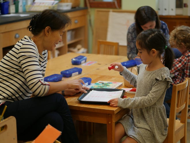 (Left to right) Willow kindergarten teacher Julie Kim of Bridgewater and Sydney Torrico of Califon work on a math game together.