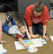 """Alyssa Brown with her son, Andrew, creating artwork based on Claude Monet's """"Bridge Over a Pond of Water Lilies,"""" as part of the Little Artists program at the Johnson-Humrickhouse Museum. The final week will have children creating artwork from felt shapes, which will be put together and displayed during the upcoming Playground of Color exhibit."""