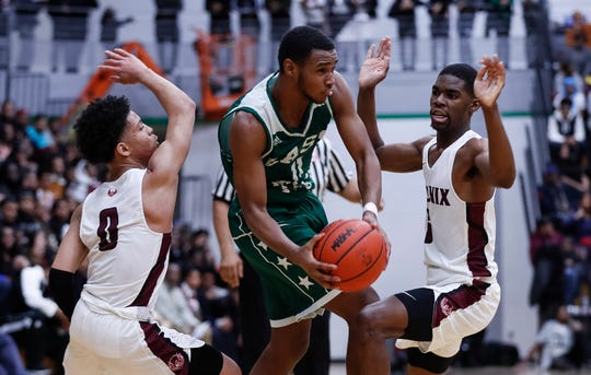 Detroit Cass Tech's Tyson Acuff tries to pass the ball against Detroit Renaissance's Keon Henderson, left, and Kaylein Marzetter during the first half of the PSL championship game at Cass Tech on Friday, Feb. 15, 2019.