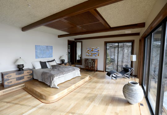 A celebration of zen, the owner's bedroom has three sides of glass with a view into treetops, white oak floors and a bed on a platform.  Asian-style wood screens over the bed push apart to reveal a glass cutout, a curving sculpture and the sky above. The home in Bloomfield Township was photographed Jan. 7, 2020.
