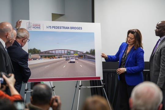 Michigan Governor Gretchen Whitmer helps turn a board with a design illustration for five pedestrian bridges over I-75 as part of the Gordie Howe International Bridge on Thursday, January 09, 2020 during a news conference in southwest Detroit.