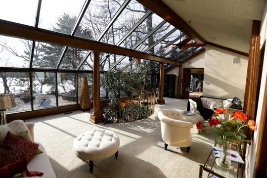 The rear wall and ceiling are replaced with glass in the Bloomfield Township home's original living room. Just outside the glass is the roof of the addition, which the owner called his Japanese garden. The long view is out to Island Lake.