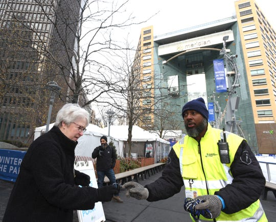 Detroit's Business Improvement Zone Ambassador Calvin Hasberry, right, gives a Back The Blue wrist band to Vera Davis, of Brighton, as she walks through Campus Martius Park, Thursday afternoon, January 9, 2020, on National Law Enforcement Appreciation Day.