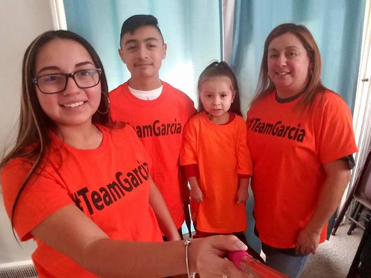 """Cindy Garcia, right, wears an orange shirt with """"#TeamGarcia"""" on it along with her daughter, Soleil, son Jorge Jr. and granddaughter. The family waited for nearly two years for Jorge Garcia to get a pardon to return to the United States."""