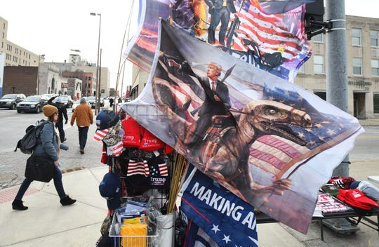 Street vendors around Huntington Center sell their Donald Trump-related wares, including an image of the president riding a dinosaur before the rally in Toledo, Ohio on January 9, 2020.