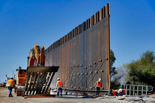 In this Sept. 10, 2019 file photo, government contractors erect a section of Pentagon-funded border wall along the Colorado River in Yuma, Ariz.