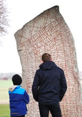 A father and a son look at a Viking-era runic stone near the Lake Vattern and the town of Odeshog, Sweden, Thursday Jan. 9, 2020.