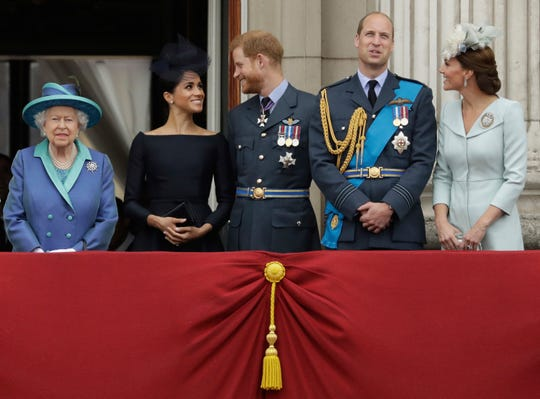 Britain's Queen Elizabeth II, and from left, Meghan the Duchess of Sussex, Prince Harry, Prince William and Kate the Duchess of Cambridge watch a flypast of Royal Air Force aircraft pass over Buckingham Palace in London in 2018.