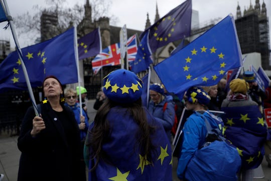 Remain in the European Union, anti-Brexit protesters hold European flags and wear European flag design berets as they demonstrate outside the Houses of Parliament in London, on the day of Prime Minister's Questions taking place inside, Wednesday, Jan. 8, 2020.