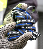 Detroit's Business Improvement Zone Ambassador Calvin Hasberry shows off several Back The Blue wrist bands he hands out to pedestrians at Campus Martius Park, Thursday afternoon, January 9, 2020, on National Law Enforcement Appreciation Day.