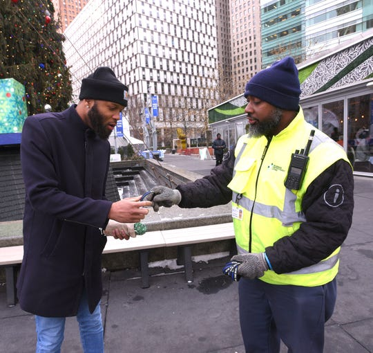 Detroit's Business Improvement Zone Ambassador Calvin Hasberry, right, gives a Back The Blue wrist band to Vince Carr, of Woodhaven, as he walk through Campus Martius Park, Thursday afternoon, January 9, 2020, on National Law Enforcement Appreciation Day.