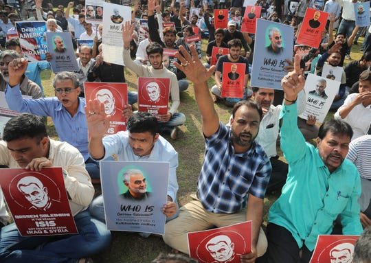 Indian Shiite Muslims hold portraits of Iranian Gen. Qassem Soleimani who was killed in a U.S. attack, as they shout slogans against the U.S. in Mumbai, India, Thursday, Jan. 9, 2020