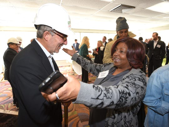 City Club Apartments Co-founder and CEO Jonathan Holtzman gets a hug from former schoolmate and current City Club Apartments resident Regina Owens after the program.