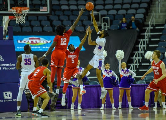 Evansville's K.J. Riley (33) shoots over the Bradley defense as the University of Evansville Aces play the Bradley University Braves at the Ford Center Wednesday evening, January 8, 2020.