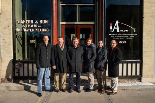 J. F. Ahern Co.'s current management committee stands outside the storefront at 17 S. Main St. The company purchased a storefront in the building in which D. Ahern & Son first opened to celebrate the 140th anniversary. The space will be transformed into late 1800s/1900s style. Pictured are, from left: Adam Wunderlin, Tony Ahern, Tripp Ahern, Krista Ebbens, Tim Schneider and Jace Hierlmeier. Not pictured: Jim Jarvis.