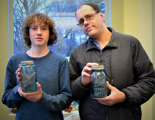 Zach Wilson and his son, Payden Wilson, with two of the vintage Ball canning jars they found.