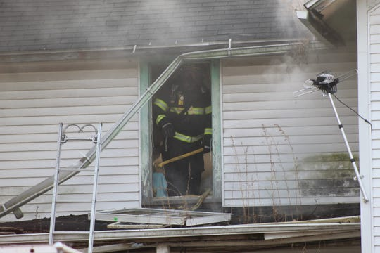 A Fremont firefighter breaks windows at a home on Sandusky Avenue to let the smoke funnel out of the house after the building caught fire Thursday morning.