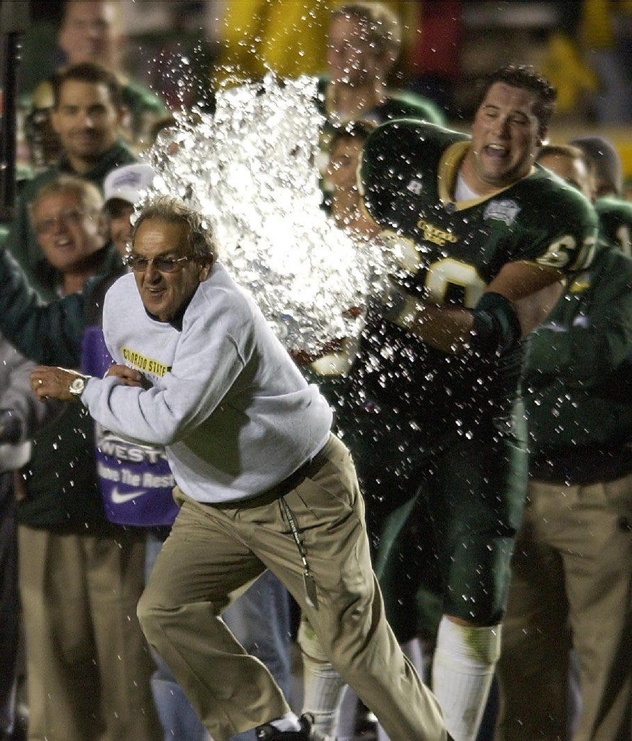 Sonny Lubick runs as player Jamie Amicarella tries to give him a celebratory ice bath. Lubick led the Rams to six conference championships and nine bowl games.