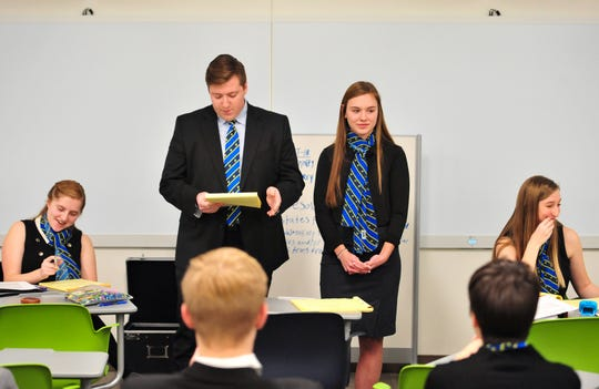 Avery Holden, center left, cross-examines the arguments of Alexis Wigdorski, center right, during the Great Falls Central Catholic speech and debate team practice on Wednesday evening, January 8, at the University of Providence.