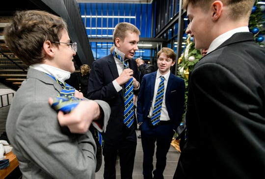 Members of The Great Falls Central Catholic High School speech and debate team practice tying their ties before their team practice at University of Providence on Wednesday evening, January 8.  Great Falls Central will host a debate meet at the University of Providence this weekend.