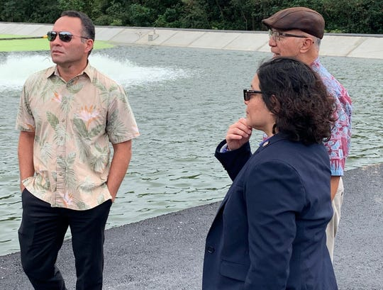 Consolldated Commission on Utilities member Mike Limtiaco, left, commission Chairman Joseph Duenas, rear, and Sen. Sabina Perez, foreground, stand at the edge of the sewage treatment lagoon Jan. 9 at the Umatac-Merizo Wastewater Treatment Plant.