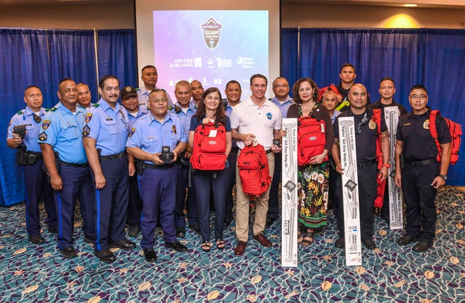 Ben Ferguson, center, Pacific Islands Club general manager, is flanked by Sen. Therese Terlaje, left, Pilar Laguaña, Guam Visitors Bureau president, and CEO, right, and members of Guam's Police Department and Guam Fire Department at a presentation at the Tumon resort Jan. 9. A collection of duty belts with accessories, vehicle lockout kits, medical backpacks and tourniquets were presented to the emergency responders for their support of the United Airlines Guam Marathon over the years.