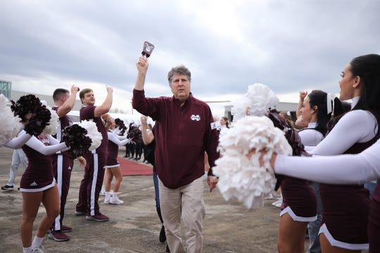 Mississippi State head coach Mike Leach is welcomed by cheerleaders at the airport in Starkville. Leach was hired as the program's 34th head coach Thursday afternoon.