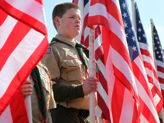 Boy Scout Troop 246 member Daniel Benson stands at attention while holding a flag bearing the name of Staff Sgt. Mark Edwards during the Field of Flags Service of Remembrance outside Parkway Presbyterian Church Saturday, Feb. 13, 2010.  Each member of troop carried a flag representing an east Tenn. soldier who was killed in either Afghanistan or Iraq.